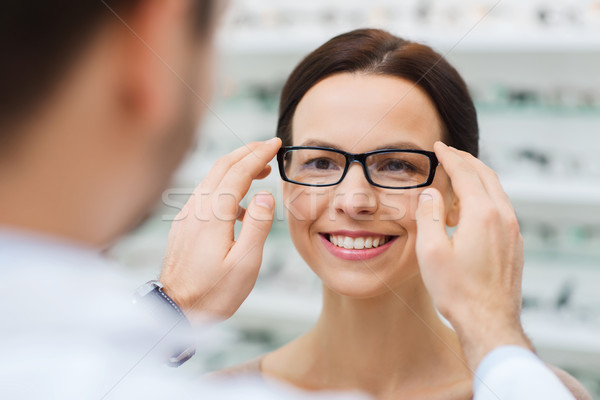 optician putting glasses to woman at optics store Stock photo © dolgachov