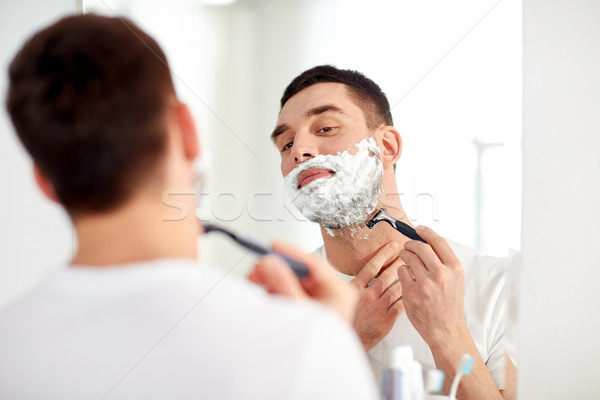 man shaving beard with razor blade at bathroom Stock photo © dolgachov