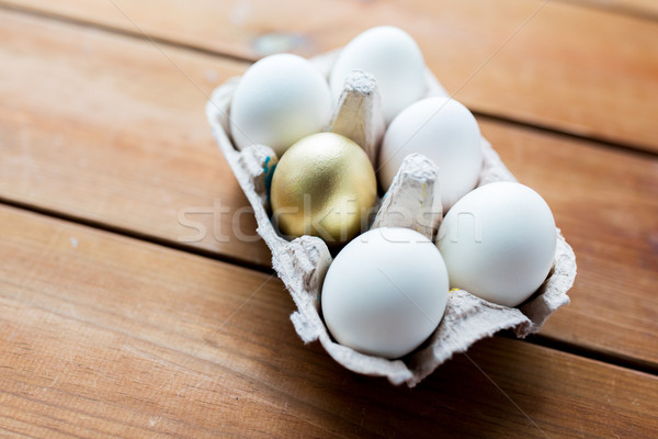 close up of white and gold eggs in egg box Stock photo © dolgachov