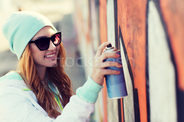 teenage girl drawing graffiti with spray paint Stock photo © dolgachov