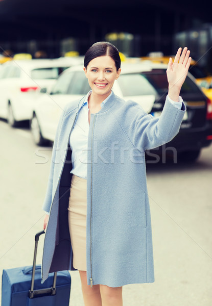 smiling young woman with travel bag waving hand Stock photo © dolgachov