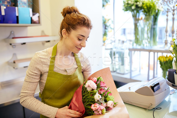 smiling florist woman packing bunch at flower shop Stock photo © dolgachov