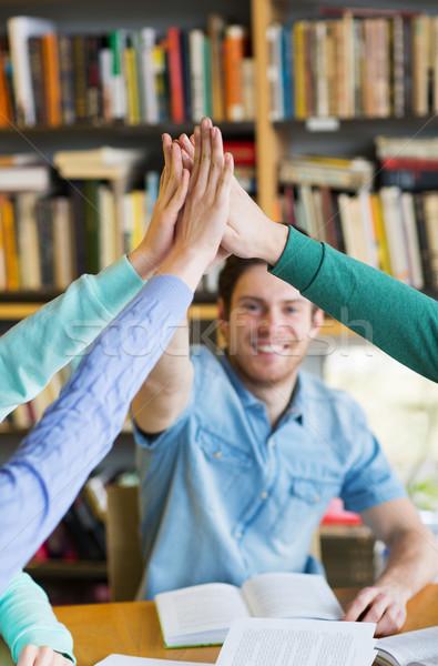 élèves livres high five bibliothèque personnes Photo stock © dolgachov