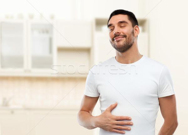 happy full man touching tummy over kitchen Stock photo © dolgachov