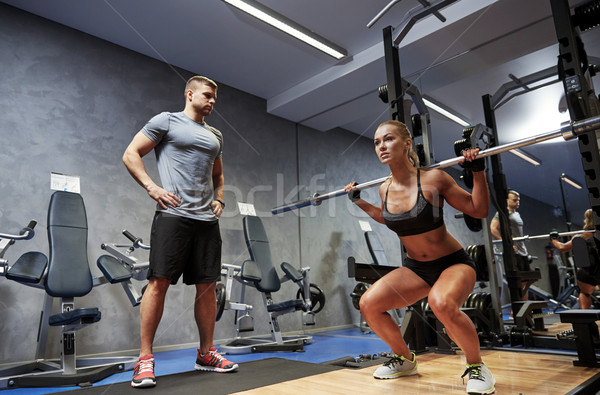 man and woman with barl flexing muscles in gym Stock photo © dolgachov