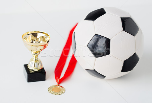 close up of football ball, golden cup and medal Stock photo © dolgachov