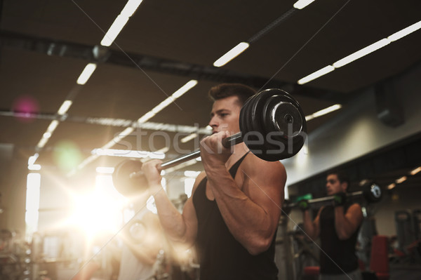 young men flexing muscles with barbells in gym Stock photo © dolgachov