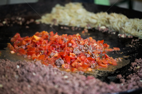 vegetables frying on big wok pan at street market Stock photo © dolgachov