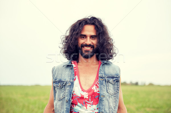 smiling young hippie man on green field Stock photo © dolgachov
