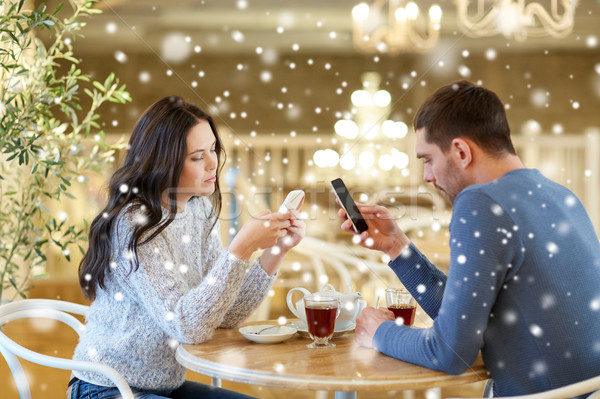 couple with smartphones drinking tea at cafe Stock photo © dolgachov