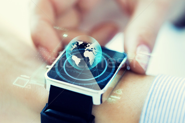 close up of hand with globe hologram on smartwatch Stock photo © dolgachov