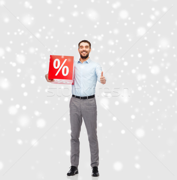 smiling man with red percentage sign over snow Stock photo © dolgachov