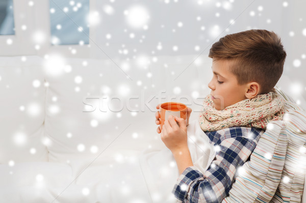 ill boy with flu in scarf drinking tea at home Stock photo © dolgachov