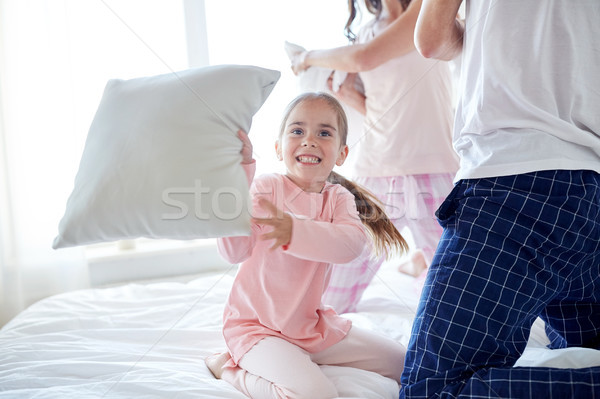 happy family having pillow fight in bed at home Stock photo © dolgachov