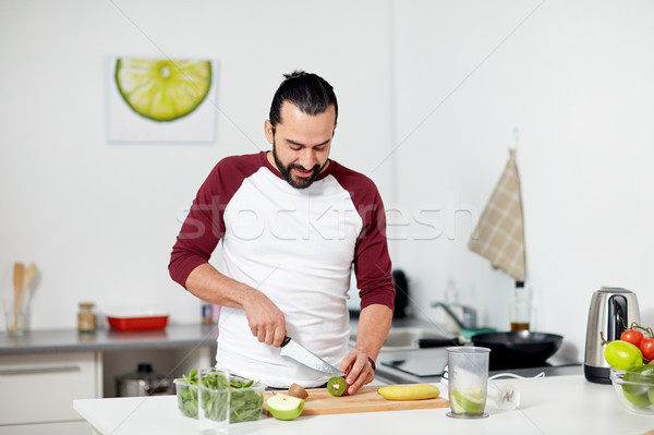 man with blender and fruit cooking at home kitchen Stock photo © dolgachov
