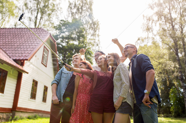 friends taking selfie at party in summer garden Stock photo © dolgachov