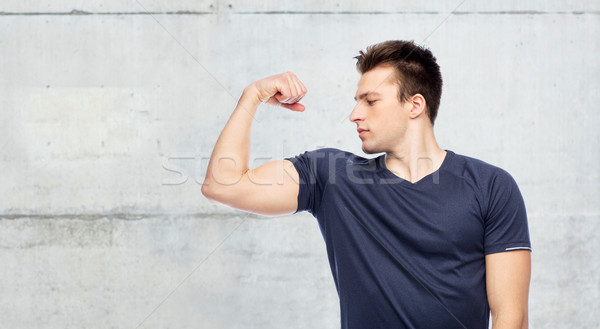 sportive man showing bicep power Stock photo © dolgachov