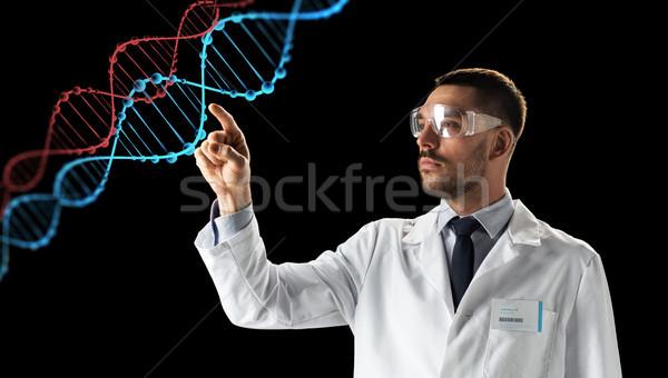 scientist in goggles with dna molecule Stock photo © dolgachov