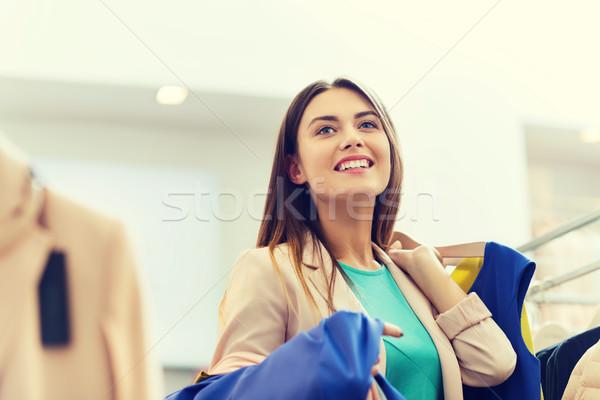 Feliz mulher jovem escolher roupa shopping venda Foto stock © dolgachov