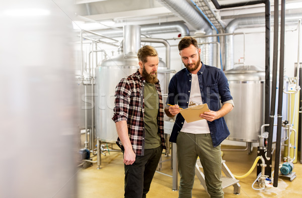 Stock photo: men with clipboard at craft brewery or beer plant