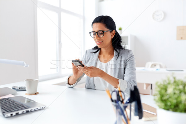businesswoman messaging on smartphone at office Stock photo © dolgachov