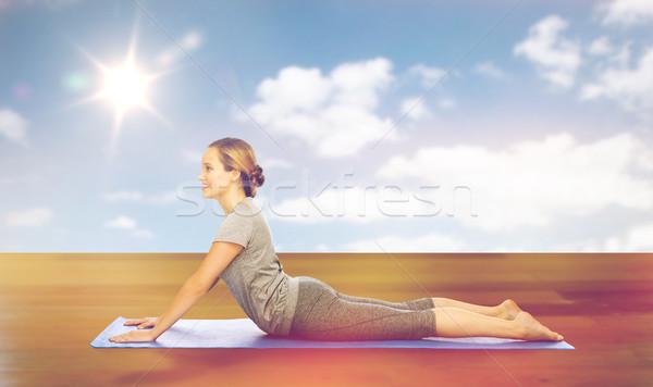 woman making yoga in dog pose on mat Stock photo © dolgachov