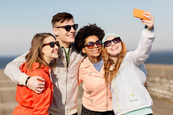 happy friends taking selfie by smartphone outdoors Stock photo © dolgachov