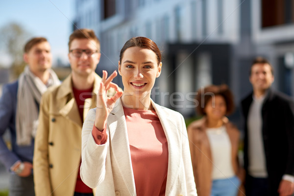happy smiling woman showing ok hand sign outdoors Stock photo © dolgachov