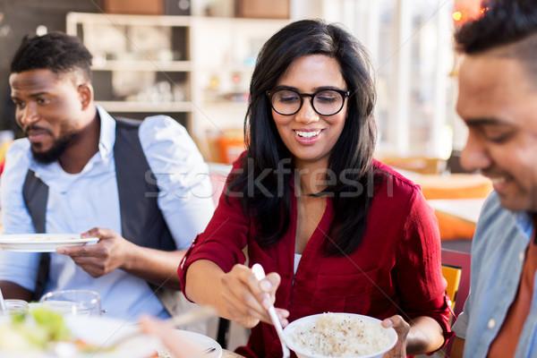 happy friends eating at restaurant Stock photo © dolgachov