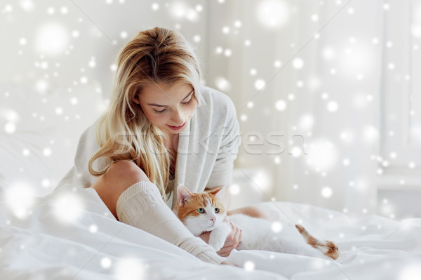 happy young woman with cat in bed at home Stock photo © dolgachov