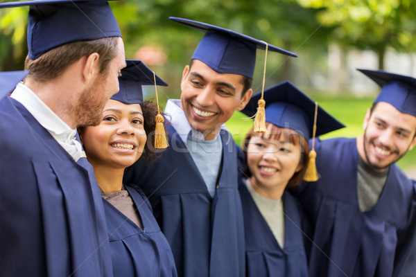 happy students or bachelors in mortar boards Stock photo © dolgachov