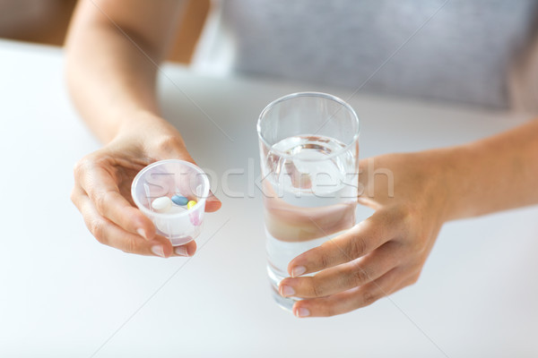 close up of hands with pills and glass of water Stock photo © dolgachov