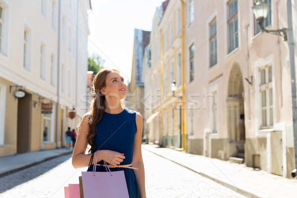 happy woman with shopping bags on city street Stock photo © dolgachov