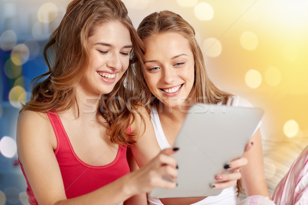 happy friends or teen girls with tablet pc at home Stock photo © dolgachov