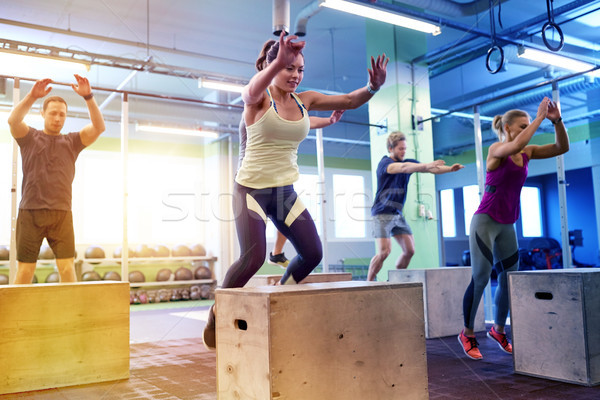 group of people doing box jumps exercise in gym Stock photo © dolgachov