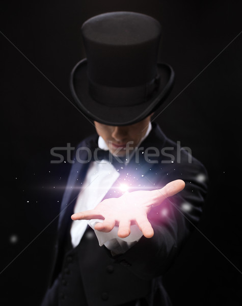 magician holding something on palm of his hand Stock photo © dolgachov