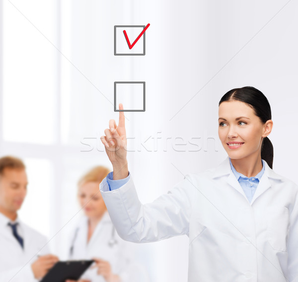 smiling female doctor pointing checkbox Stock photo © dolgachov
