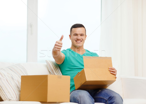 man with cardboard boxes at home showing thumbs up Stock photo © dolgachov