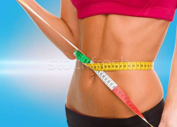 close up of trained belly with measuring tape Stock photo © dolgachov