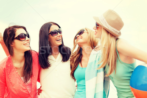 smiling girls with ball and towel on the beach Stock photo © dolgachov