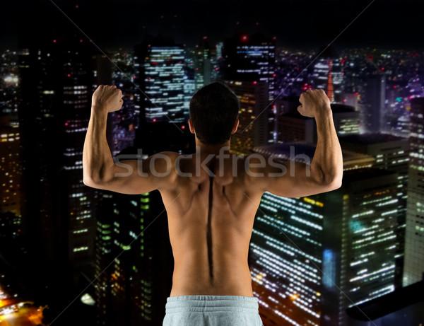 Jonge man tonen biceps spieren sport bodybuilding Stockfoto © dolgachov