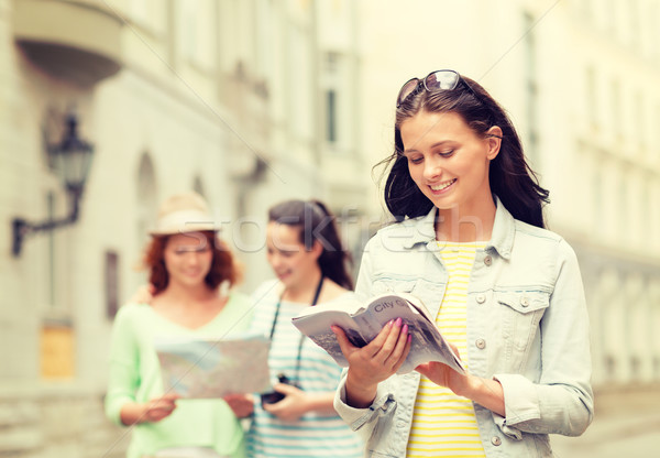 smiling teenage girls with city guides and camera Stock photo © dolgachov