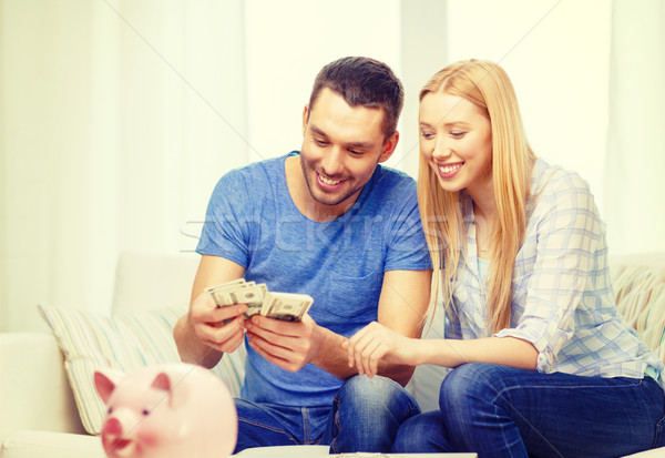 smiling couple counting money at home Stock photo © dolgachov