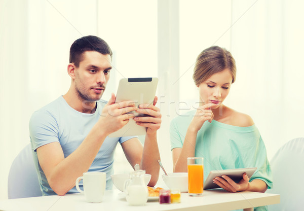 Stock photo: concentrated couple with tablet pc reading news