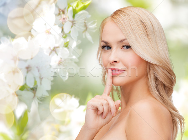 Stock photo: beautiful young woman pointing finger to lips