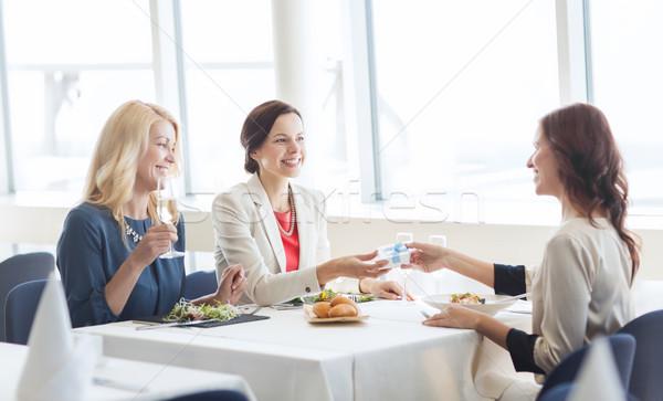 happy women giving birthday present at restaurant Stock photo © dolgachov