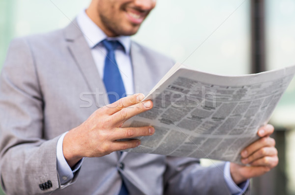 Stock photo: close up of smiling businessman reading newspaper