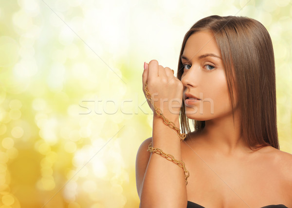 woman wearing golden necklace over yellow lights Stock photo © dolgachov