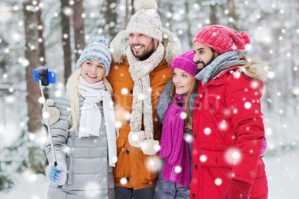 smiling friends with smartphone in winter forest Stock photo © dolgachov