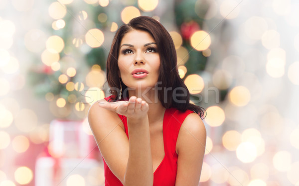 woman sending blow kiss  over christmas lights Stock photo © dolgachov